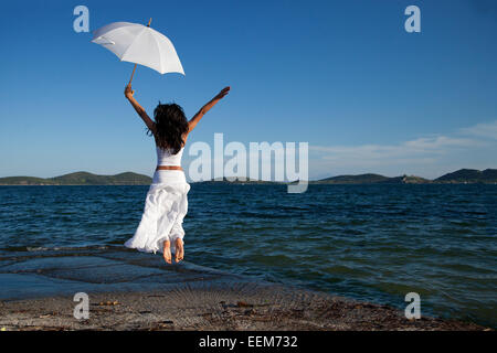 Young woman in white holding umbrella jumping on beach - Stock Photo