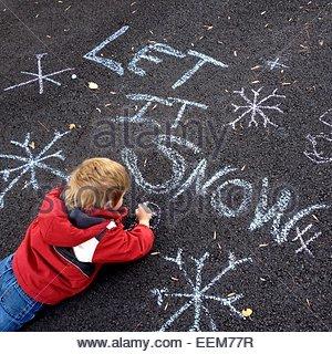 Boy lying on asphalt, drawing with chalk - Stock Photo