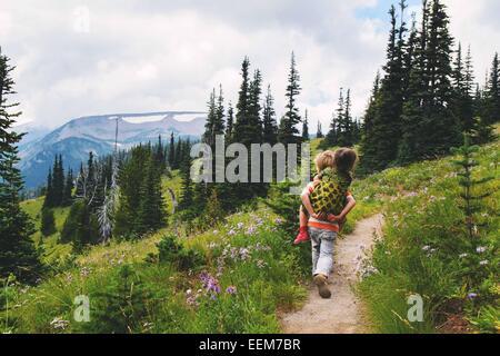 Boy walking along a mountain trail giving his sister a piggyback ride, USA - Stock Photo