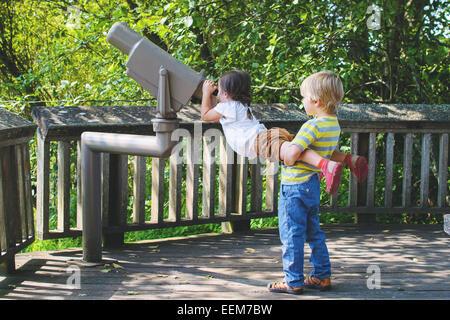 Young boy (4-5) helping girl (2-3) looking through telescope - Stock Photo