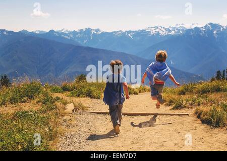 Two boys dressed as superheroes running along a mountain trail - Stock Photo