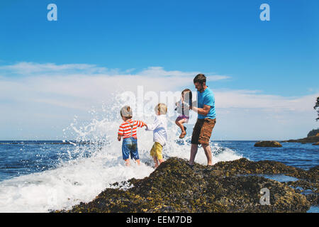 Father standing on rocks playing in the waves with his three children, USA - Stock Photo