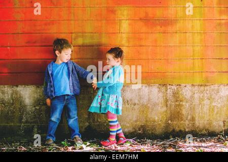 Young boy and girl (2-3) holding hands - Stock Photo
