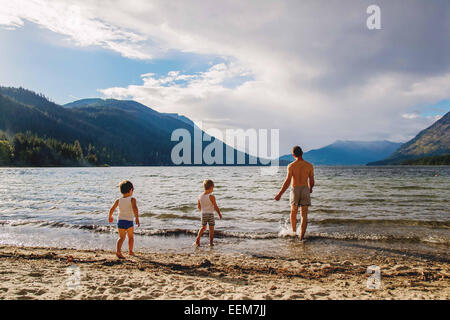 Father and sons (2-3,4-5) going swimming - Stock Photo
