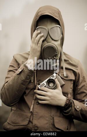 Man with analog camera wearing gas mask - Stock Photo