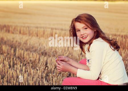Girl (6-7) in cornfield - Stock Photo