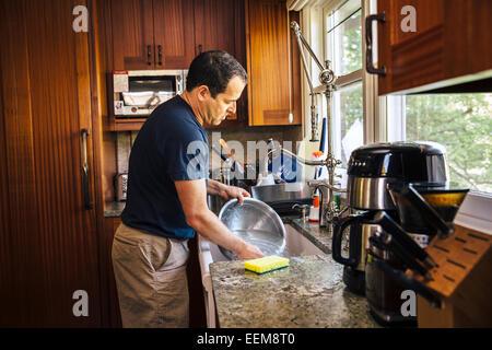 Caucasian man washing dishes in kitchen - Stock Photo