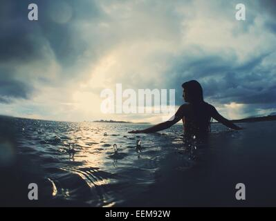 Silhouette of a woman standing in the sea in the rain - Stock Photo