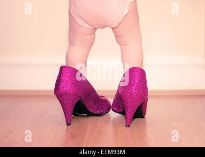 Toddler wearing mother's shoes - Stock Photo