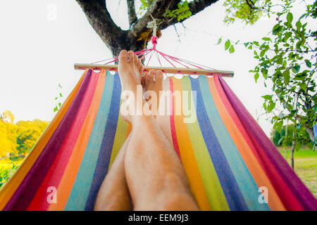Detail of men feet relaxing in colorful hammock - Stock Photo