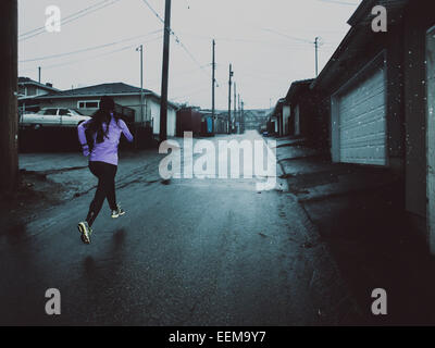 Young woman running along street at dusk - Stock Photo