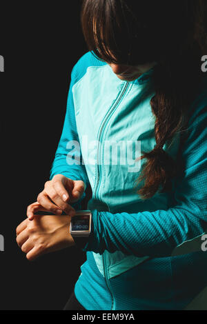 Young woman looking at smart watch - Stock Photo
