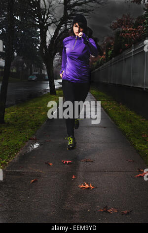 Young woman running along city sidewalk after rain - Stock Photo