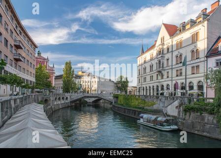 Buildings and pedestrian bridge over urban canal, Ljubljana, Central Slovenia, Slovenia - Stock Photo