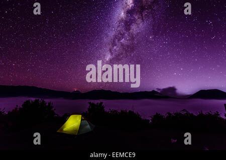 Milky Way galaxy over campsite in starry night sky - Stock Photo