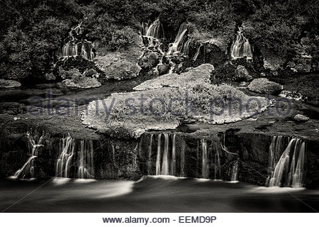 Waterfall flowing over rock formations to lake - Stock Photo
