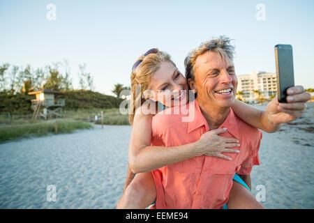 Older Caucasian couple taking cell phone selfie on beach