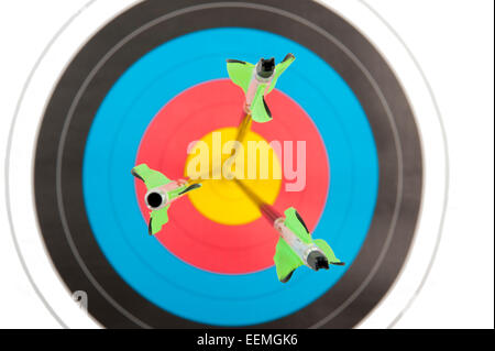 Three arrows hitting the bull's eye of an archery target in short dept of field - Stock Photo