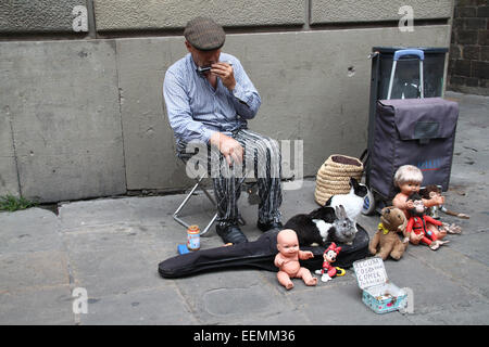 Elderly street entertainer with rabbits and old toys, playing the harmonica, near the Cathedral in Barcelona, Catalonia, - Stock Photo