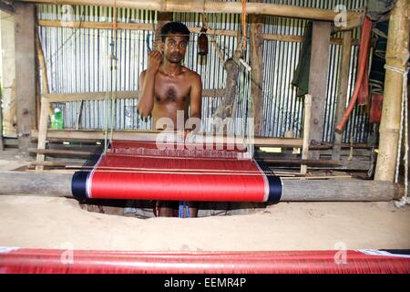 Bangladesh 10 January 2015. A Tribal man weaving cloth on an old traditional loom. - Stock Photo