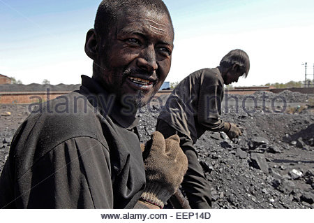 Workers sort and separate smoke, coal and anthracite (smoke-free coal) at a coal mine near Yinchuan (Ningxia province). - Stock Photo