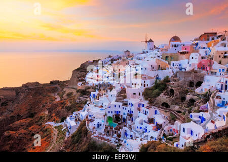 Vibrant sunset over houses and villas at Oia Santorini Greece - Stock Photo