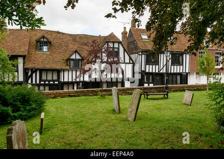 view of old wattle houses and gravestones in church cemetery in small  historic village of Rye, East Sussex - Stock Photo