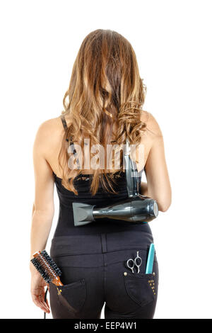Professional caucasian brunette female hairdresser posing from behind with hairdryer on her back with brush and - Stock Photo