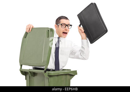 Terrified businessman hiding in a trash can isolated against white background - Stock Photo