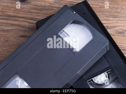 Image shows two old retro video tapes on a wooden table - Stock Photo