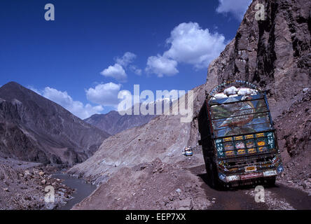 Karakorum Highway in Pakistan, a painted and decorated truck fills the road in Himalayas on road to northern areas - Stock Photo