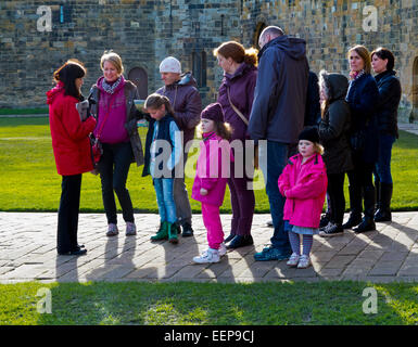 Guide taking a group of tourists on a tour of Alnwick Castle the location some of the Harry Potter films in Northumberland - Stock Photo