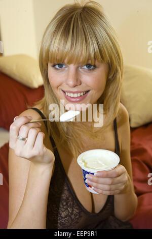 Frau, jung, junge, Schlafzimmer, Detail, Bett, sitzen, Yoghurt, essen, innen, froehlich, Freude, Fruehstueck, fruehstuecken, - Stock Photo