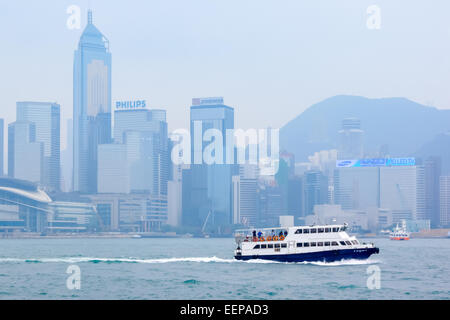 Boat on Victoria Harbour with high rise skyscrapers of Hong Kong in the background. - Stock Photo