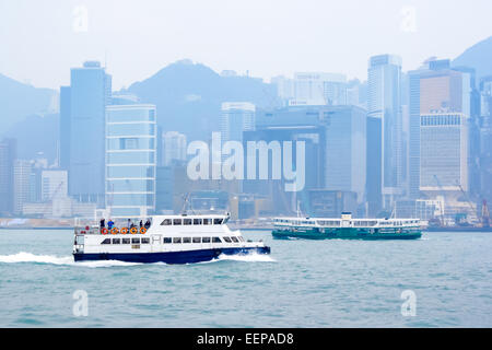 Boat and Star Ferry on Victoria Harbour with high rise skyscrapers of Hong Kong in the background. - Stock Photo