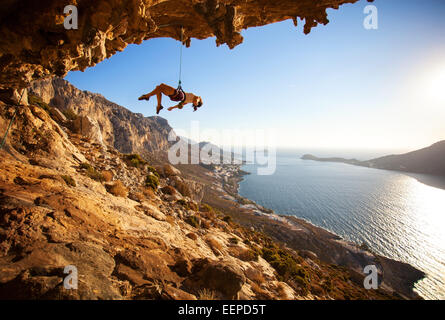 Female rock climber hanging on rope after unsuccessful attempt to take next handhold on cliff while lead climbing - Stock Photo