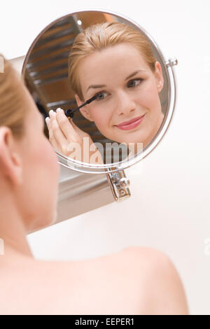 Young pretty woman doing makeup, using mascara (Modellfreigabe) - Stock Photo