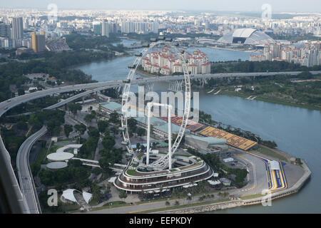 Singapore Flyer. Giant ferris wheel in Singapore. As seen from the Sky View Park of the Marina Bay Sands Hotel and - Stock Photo