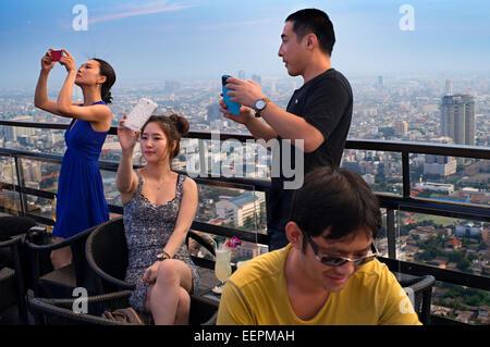 Asian people taking pictures. Banyan Tree Rooftop Vertigo & Moon Bar, Restaurant, , Bangkok , Thailand. View of - Stock Photo