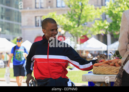 Man in wheelchair with Spinal Meningitis shopping at vegetable stand in the city - Stock Photo
