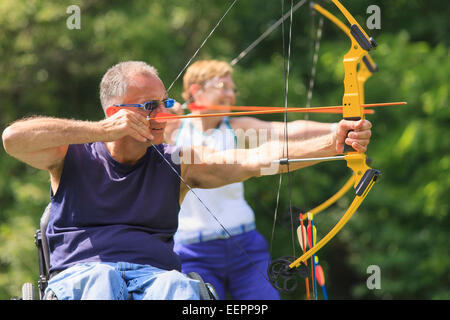 Man with spinal cord injury and woman with prosthetic leg aiming arrows at target - Stock Photo