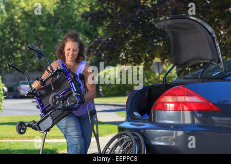 Woman with Spina Bifida taking apart wheelchair to put it in the back of car - Stock Photo