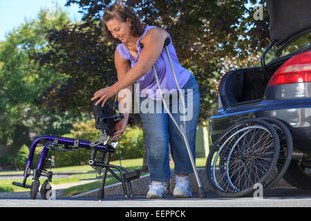 Woman with Spina Bifida using crutches to take wheelchair apart for traveling in the car - Stock Photo