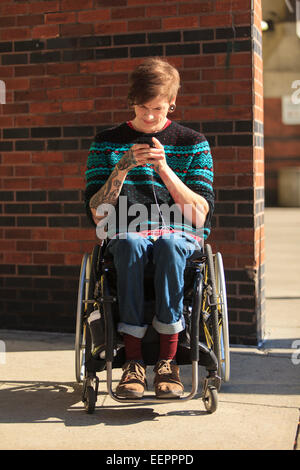 Trendy man with a spinal cord injury in wheelchair taking his text messages - Stock Photo