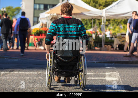Trendy man with a spinal cord injury in wheelchair at a city outdoor market - Stock Photo