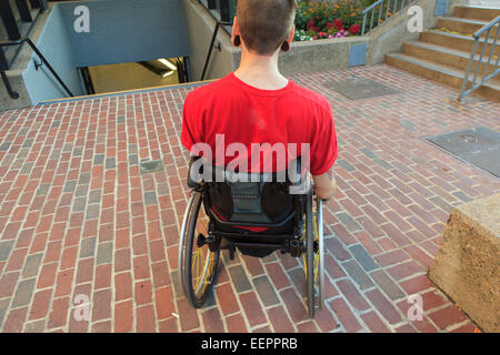 Trendy man with a spinal cord injury in wheelchair planning his access to the subway - Stock Photo