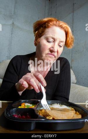 Unhappy woman eating a TV dinner - Stock Photo