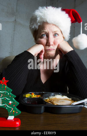 Unhappy woman wearing a christmas stocking hat eating a turkey TV dinner on a tray table in the basement - Stock Photo
