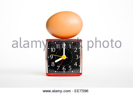 Boiled egg on top of alarm clock against white background with copy space - Stock Photo