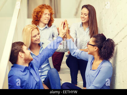team doing high five gesture sitting on staircase - Stock Photo